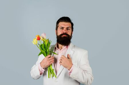 Romantic. Bearded man hold bouquet of flowers. Valentines Day, Womens Day. Birthday. Handsome man holds flowers. Bouquet of tulips. Celebration