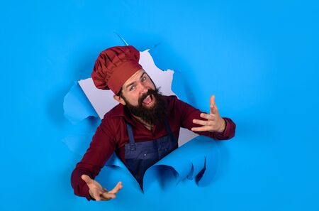 Bearded man in chef uniform looking through paper hole. Professional happy man chef. Cooking, profession and business. Professional approach to business. Male chef, cook or baker in hat and apron
