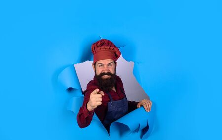 Bearded man through paper. Chef. Professional chef points forward. Bearded cook in kitchen. Chief man in cook uniform. Discount. Sale Banco de Imagens