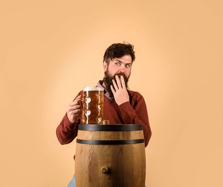 Attractive bearded brewer with wooden barrel of beer and mug of beer. Beer time. Oktoberfest festival. Holliday, drinks, alcohol and leisure concept. Bearded man hold glass and barrel with craft beer Stok Fotoğraf