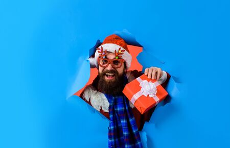 Man through paper. Discount. Sale. Christmas sales. Bearded Santa Claus holds present. Christmas decorations. Delivery gifts. New year gift. Space for text. Holiday poster design, banner Banque d'images