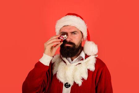 Santa Claus holds crystal ball. Christmas snowglobe in hand. Bearded Santa with small Christmas snow globe. Decoration element. Christmas decoration. Surprised Santa man holds snow ball near eye Stock fotó