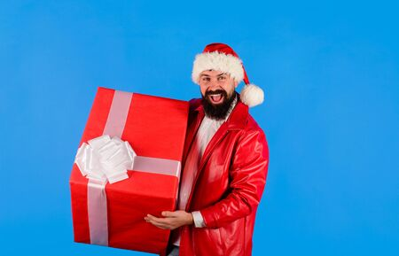 Man in Santa hat holds gift box. Christmas. New year gifts. Santa Claus holds big present. Smiling Santa Claus with New Year gift. New year gift. Present box. Merry christmas. Delivery gifts.