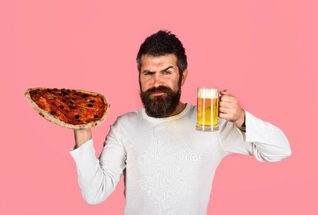 Satisfied man with beard and mustache enjoying delicious pizza in cafe. Fast food. Italian food. Pizza delivery concept. Bearded man holds tasty pizza and beer. Pizza time. Food and diet concept