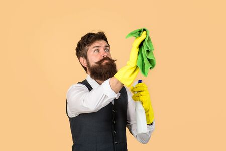 Professional cleaning man in uniform. Male janitor with cleaning equipments. Bearded man in uniform, rubber gloves with cleaning products. Domestic service cleaner man with rag and cleaner spray Reklamní fotografie