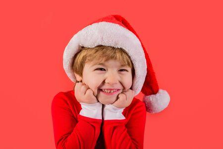 Santa helper. Elf. Smiling kid in Santa costume. Santa Claus. Gifts. New Year. Christmas kids. Holiday. Kid in santa hat. Christmas. New year kid. Close up. Stock Photo - 132114487