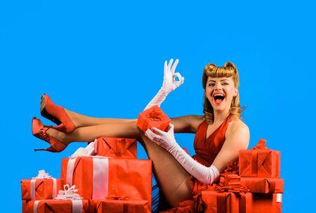 别针与礼物盒的女孩显示好标志。红色礼服的妇女有减速火箭的发型的。圣诞节。新年。情人节。女人的日子。母亲节。生日。礼物。礼物盒。 Celebration. Black Friday