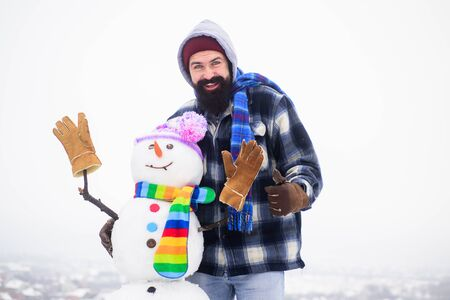 Happy holiday&celebration. New year snowman in knitted hat&striped scarf. Man in winter clothes raised thumb up. Happy man hugs snowman. Winter man standing near snowman. Bearded man shows thumb up Foto de archivo
