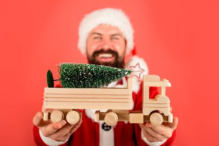 Santa man hold toy car with Christmas tree. Selective focus on car. Christmas tree on wooden toy truck car. Christmas story. Santa Claus with fir-tree. Christmas holiday celebration. New Year concept Stok Fotoğraf - 132114809