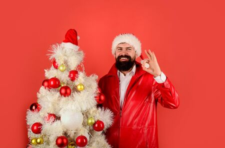 Business man in Santa hat near white Christmas tree. Bearded man ready for Christmas. Santa Claus with New Year fir-tree. Santa Claus man shows ok sign. Christmas, Winter holiday, New Year. Pine tree Banco de Imagens - 132114397