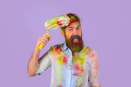 Professional painter, decorator, builder worker. Handsome bearded worker with paint roller and hard hat. Repair, building concept. Painter. Repairman, tradesman, handyman with paint roller and helmet