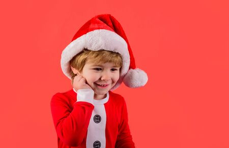 Happy boy in Santa costume. Smiling boy in Santa Claus hat. Christmas time. Santa helper. Little kid in Santa costume. Merry christmas. Happy New Year. Christmas kid in red hat. New Year's holidays
