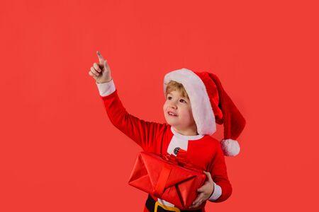 Gift. Santa helper. Elf. Little klid in Santa costume holds presetn. Santa Claus. Gifts. New Year. Happy New Year. Christmas. Eve. Holiday. Kid in santa hat. Christmas. New year kid. Close up Stock Photo
