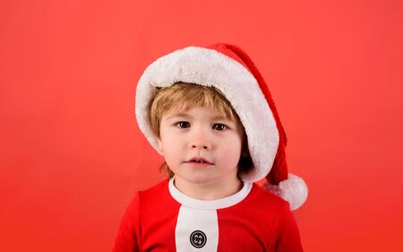 Merry christmas. Happy New Year. Surprised boy in Santa costume. Christmas kid in red hat. New Years holiday. Little boy in Santa Claus hat. Christmas time. Santa helper. Little kid in Santa costume