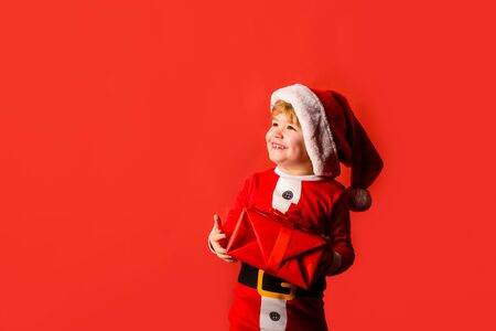 Christmas children. Little kids celebrating Christmas. Child with Christmas present. Happy child in Santa costume. Little Santa Claus gifting gift. Cute boy in santa hat. New year kid. Happy new year