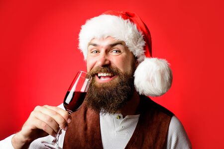 Santa man drink glass of red wine. Businessman in Santa hat hold glass of wine. Bearded man tasting red wine. New year party. Smiling man in Santa costume. Holidays, christmas and celebration concept Stockfoto