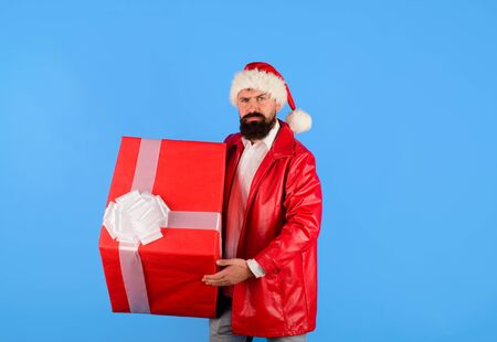 Gifts delivery service. Bearded man in Santa Claus hat holds gift box. Christmas gift. Christmas or New Year holidays. Man with Christmas gift box. Santa christmas man in red jacket hold gift present Standard-Bild