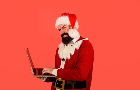 Christmas shopping concept. Bearded man in santa hat with notebook. Modern technology. Communication. Santa Claus using laptop. Santa claus shopping online with laptop. Buy christmas gifts online Stock Photo