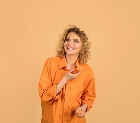 Vegetarian food, diet, dieting. Beautiful girl eating carrot. Happy woman with organic carrot. Vegetable having good impact on teeth. Enjoying healthy food. Smiling woman bites carrot. Healthy eating