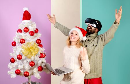 Bearded man in VR glasses. Woman with laptop. Virtual reality. 3d technology. Happy couple celebrate Christmas. Family in near Christmas tree. Winter holidays. Christmas. New Year. Christmas couple