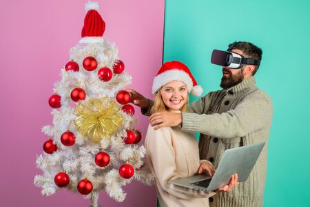 Christmas couple. Bearded man in VR glasses. Woman with laptop. Virtual reality. 3d technology. Winter holidays. Christmas. New Year. Happy couple celebrate Christmas. Family in near Christmas tree