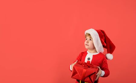 Little Santa Claus holds gift. Happy child in Santa costume. New year kid. Cute boy in santa hat. Christmas children. Little kids celebrating Christmas. Child with Christmas present. Happy new year