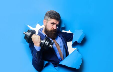 Businessman with dumbbell looking through paper hole. Power. Strength. Sport. Sporty bearded man with dumbbell. Fitness with equipment. Workout. Healthy lifestyle. Discount. Season sales. Copy space