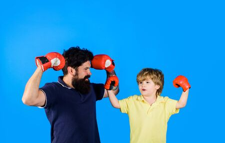 Boxer trainer is training new little boy boxer for competitions. Little boxer boy exercising at boxing with coach. Father ready to fight with son doing boxing exercise. Kid and coach in boxing gloves Reklamní fotografie