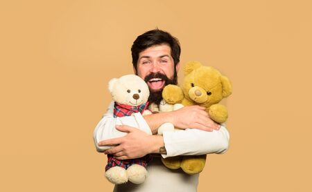 Gift and present concept. Happy bearded man with plush toy. Present for birthday. Bearded man hugging teddy bear. Teddy bear. Birthday or anniversary and holiday celebration. Male with teddy bear Stock fotó