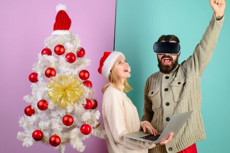 New Year, Christmas, future and technology concept. 3d technology, virtual reality, entertainment. Woman in santa hat with laptop. Bearded man in virtual 3D glasses at christmas. Virtual reality mask Stok Fotoğraf