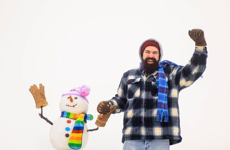 Man in winter clothes standing near snowman. Bearded man holds snowman by hand. Wintertime. Winter fashion. Snowman in hat, scarf, gloves. Happy holiday. Bearded man with snowman. Christmas snow man