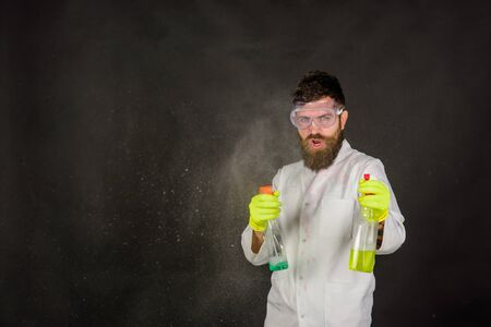 Bearded man with cleaning equipment. Bearded man with cleaning spray. Bearded man in uniform and rubber gloves holds cleanser spray. Cleaning advertising. Cleaners. Cleaning service and work concept Banco de Imagens