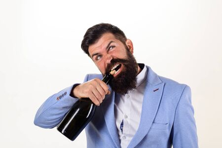 Bearded man trying to open bottle of wine. Bad habits. Sexy male model pulls out cork with teeth with bottle of wine. Brutal handsome man opens his teeth bottle of champagne. Champagne or wine bottle Stok Fotoğraf