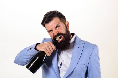 Sexy male model pulls out cork with teeth with bottle of wine. Brutal handsome man opens his teeth bottle of champagne. Champagne or wine bottle. Bearded man trying to open bottle of wine. Bad habits