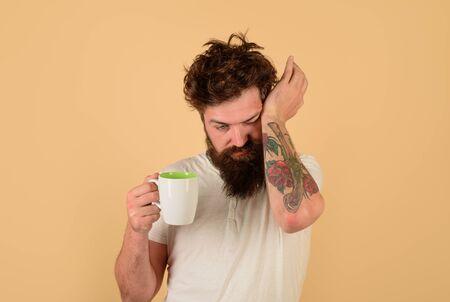 Sleepy man. Awaking. Cup of coffee. Tired guy hold coffee mug. Man hold mug with hot drink. Sleepy man with cup of coffee. Cup of coffee. Morning refreshment Archivio Fotografico - 134339790