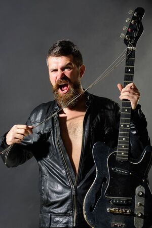 Music party, entertainment. Rock musician with guitar. Handsome bearded in leather jacket with electric guitar. Man with beard holds musical instrument. Guitarist in jacket with electric bass guitar Archivio Fotografico - 134339793