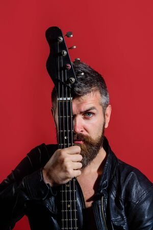 Fashionable rock guitarist playing electric bass guitar. Bearded man with electric guitar. Handsome man in black leather jacket with electric guitar. Music, instrument education and learning concept Archivio Fotografico - 134339797