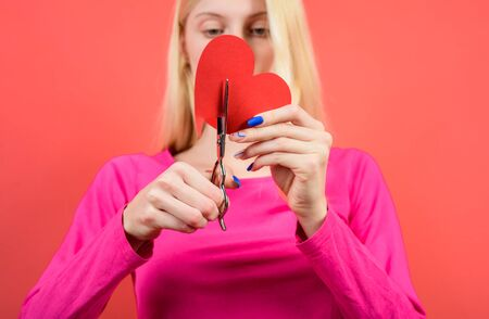 Beautiful girl cuts with scissors red heart. Concept of breaking relations, quarrels and divorce. Woman cuts heart by scissors. Pair diverges. Loss of feelings for your loved one. Bad relationships Archivio Fotografico - 134339827