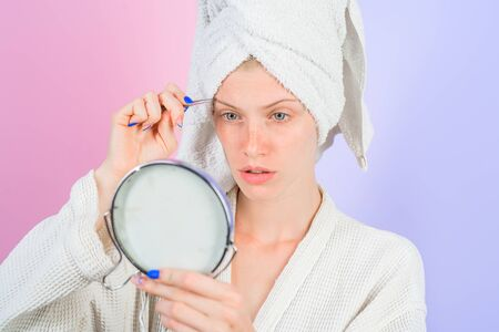 Eyebrows beauty care concept. Beauty tools. Woman pulls out eyebrows with tweezers. Correction procedure in beauty salon. Woman pluck eyebrows looking in mirror. Epilate eyebrows. Makeup process