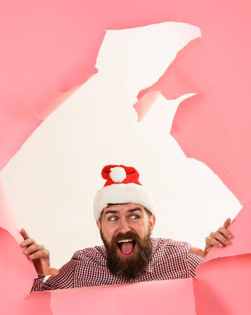 Man in Santa hat. New year. Shopping season, discount, sale. Winter holidays. Christmas sales. Winter sales, shopping concept. Happy Santa man looks through paper hole. Winter holidays&boxing day Archivio Fotografico - 134339836