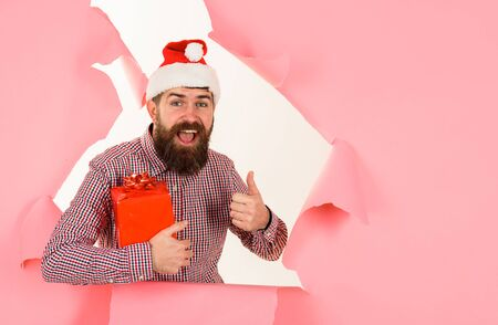 Santa man looking through hole in paper with present. Discount. Christmas sales. Bearded Santa Claus holds small Christmas gift. Christmas decorations. Space for text. Holiday poster design, banner Archivio Fotografico - 134339837