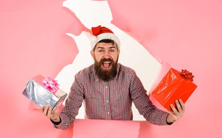 Happy man in Santa hat with presents gifts box breaks through paper wall. Christmas, New Year. Bearded man in Santa hat with gifts boxes through paper hole. Santa Claus with gifts pokes out of hole Archivio Fotografico - 134339838