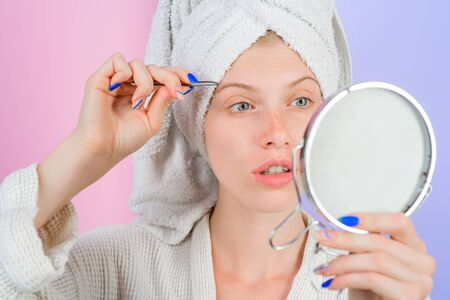 Eyebrows beauty care concept. Beauty tools. Woman pulls out eyebrows with tweezers. Correction procedure in beauty salon. Woman pluck eyebrows looking in mirror. Epilate eyebrows. Girl makeup process
