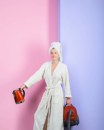 Smiling woman with vacuum cleaner and kettle. Housewife with vacuum cleaner and electric kettle in hands. Woman in bathrobe and towel on head. Happy woman with vacuum cleaner and kettle at home