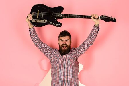 Music instrument. Guitarist through hole in pink paper holds guitar in hand. Bearded man, guitarist with electric guitar. Hobby, music instrument, entertainment. Play guitar. Electric bass guitar Archivio Fotografico - 134339851