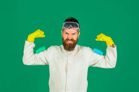 Housekeeping. Houseman in protective gloves and glasses with sponges for cleaning. Bearded man holds sponges for washing dishes. Cleaning with sponge. Cleaning supplies. Cleaner man holds sponges Foto de archivo - 134339856