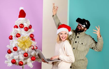 Bearded man in virtual 3D glasses at christmas. Woman in santa hat with laptop. Virtual reality mask. New Year, Christmas, future and technology concept. 3d technology, virtual reality, entertainment Archivio Fotografico - 134339859