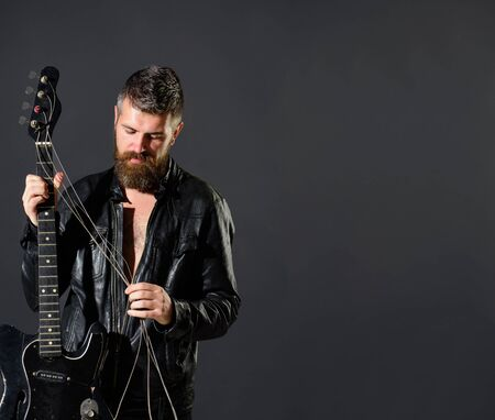 Handsome bearded in leather jacket with electric guitar. Man with beard holds musical instrument. Guitarist in jacket with electric bass guitar. Music party, entertainment. Rock musician with guitar Archivio Fotografico - 134339871