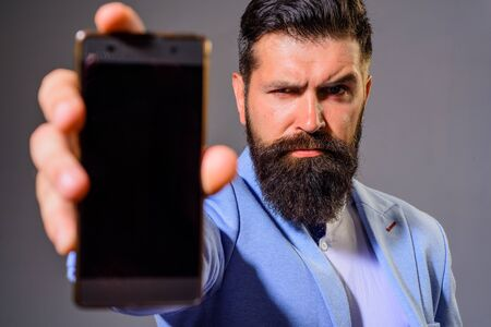 Business man shows mobile phone. Business, communication, internet, technology concept. Businessman holds smartphone. Businessman show smart phone with blank screen. Bearded man in suit showing phone Archivio Fotografico - 134339875
