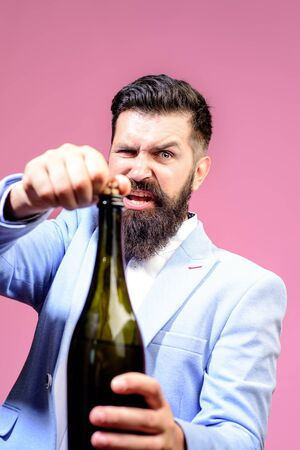 Celebration, drink, alcohol and holidays concept. Bartender opening wine bottle. Selective focus. Bearded man opens bottle. Sommelier with wine bottle. Handsome man in suit opens bottle of champagne Archivio Fotografico - 134339880